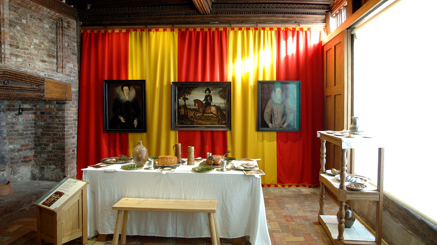 Ancient House, Hall view to feast table with three portraits of about 1600 on display,